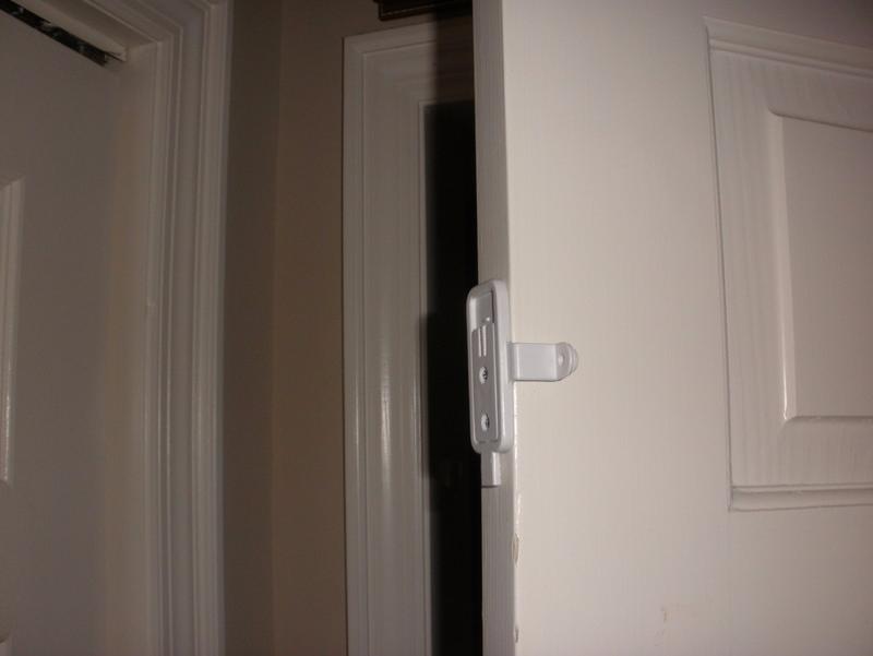 DoorSmoocher™ child safety sliding pocket and swing door latch on swing door in open position & DoorSmoocher™ Pocket Door and Swing Door Lock